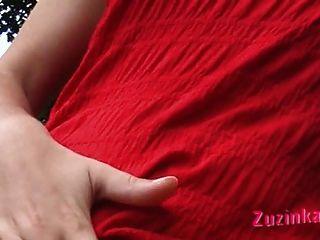 أحمر يرتدون ملابس فتاة في حديقة عامة.