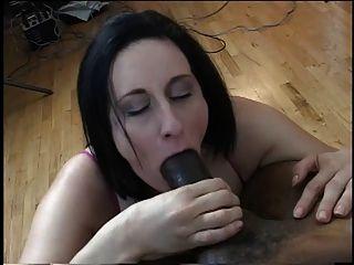 امرأة سمراء مع كبير الثدي تمتص على الديك الأسود الضخم على ركبتيها