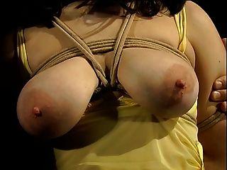 هوتي الثدي الكبير في ثوب أصفر ملزمة وحلمته مغطاة الملابس أوتاد