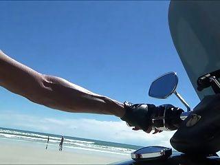 راكب الدراجة النارية الجلود مثير في الأحذية الفخذ على الشاطئ