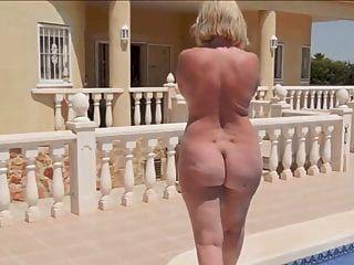 امرأة ناضجة مع الحمار جولة عارية يمشي بجوار حمام السباحة